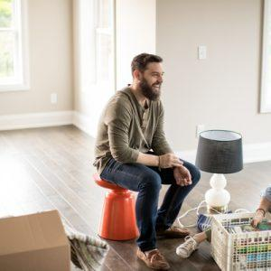 man and woman sitting around moving boxes