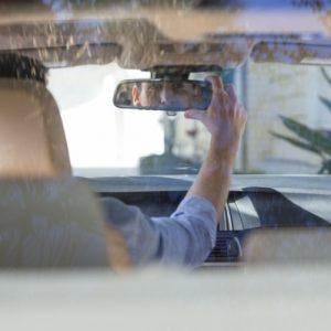 Man adjusting rearview mirror in car