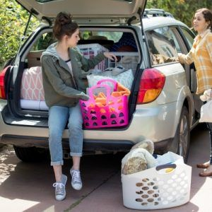 Girl sitting in back of station wagon unloading luggage