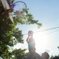 Girl and dad playing basketball.
