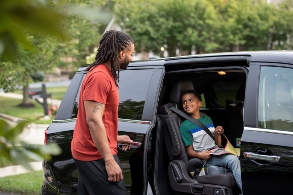 father outside of van with son buckled in seat