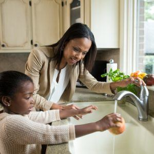 Mom and daughter washing an apple to prevent germs
