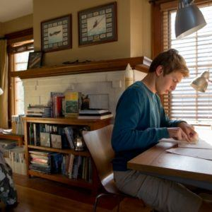 young man study at college dorm room desk