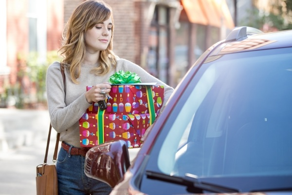 woman with gifts approaching car