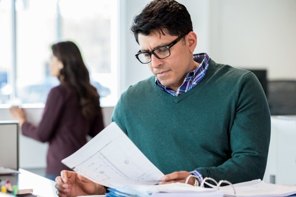 man wearing glasses and green sweater reading report