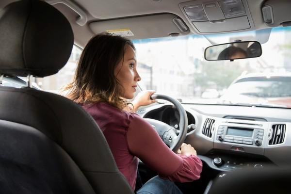 woman in purple shirt driving car
