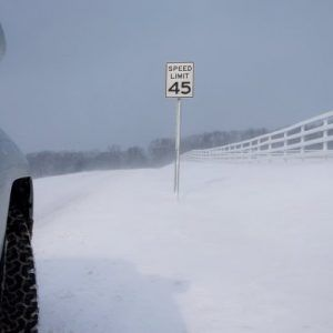 SUV on snow covered road with a 45 mph speed limit sign