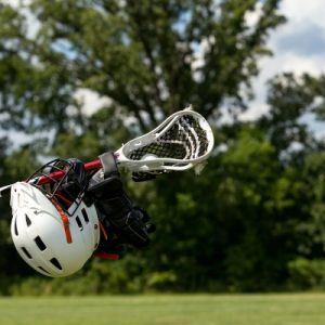 child holding lacrosse equipment
