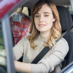 teenage girl driving and looking at her side view mirror