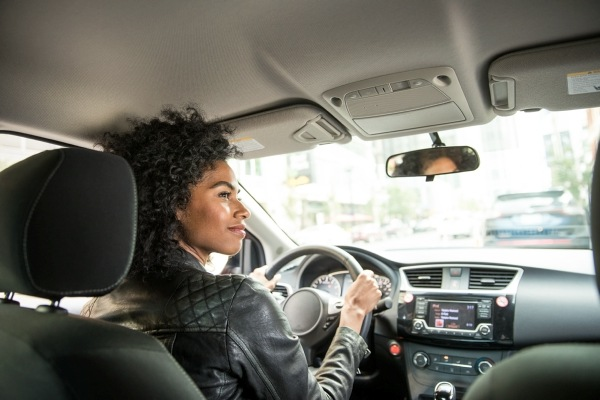 woman looking right while driving car