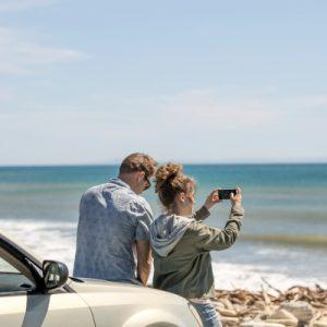 Couple standing in front of their car on the beach. Woman takes photo of the ocean.