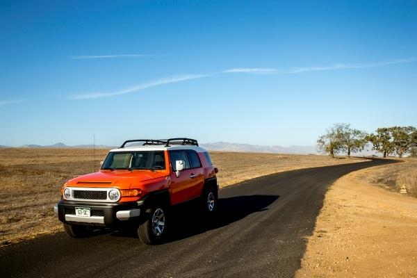 orange SUV on desert road
