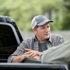 two men leaning against pickup truck talking