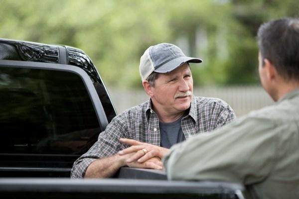 two men leaning against pickup truck talking
