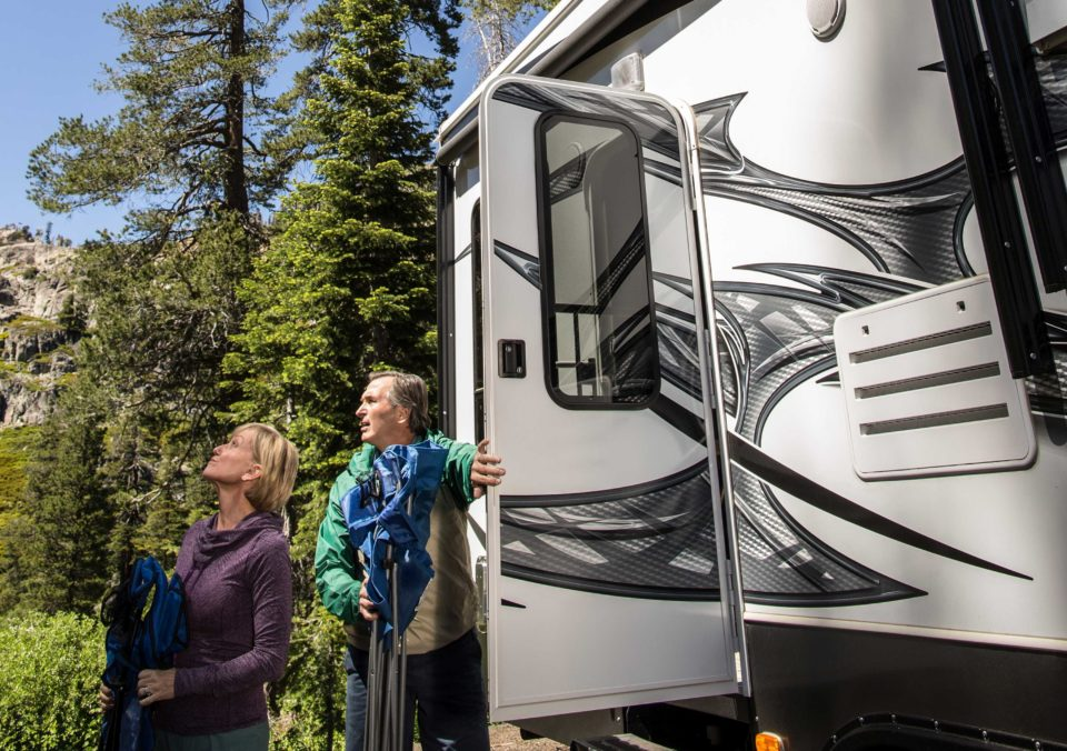 man and woman beside rv