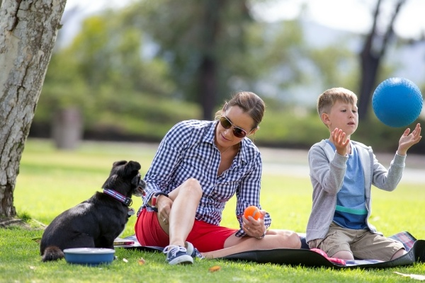 Woman and son sitting on grass with black dog