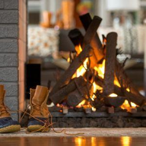 duck boots in front of a modern fireplace
