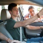 teenage boy adjusting rearview mirror while mom leans in through window