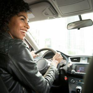 Woman wearing leather jacket driving car