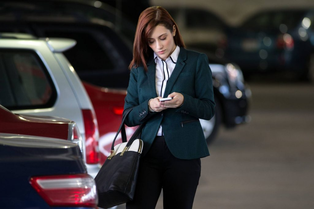 a woman checking her phone in the parking lot