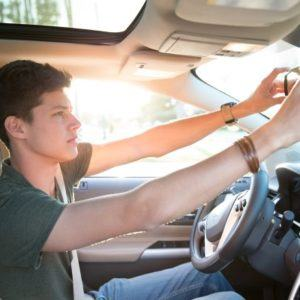 Teenage boy adjusting rear view mirror