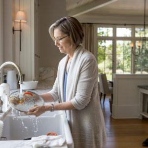 woman washing dishes in the kitchen sink