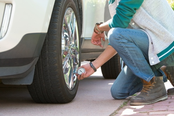 Man checking tire pressure on white car