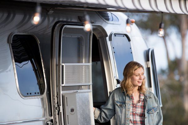 woman dressed for cool weather standing in RV doorway