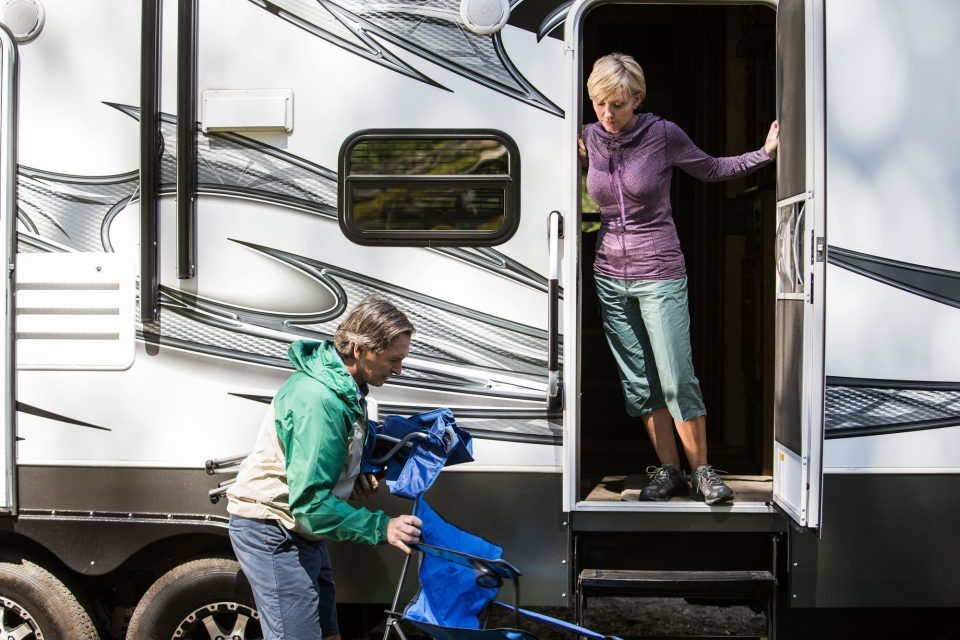 a woman opening a door to an RV