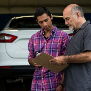 men looking at clipboard next to car