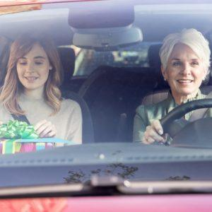 Older woman driving car while younger woman holds present in passenger seat