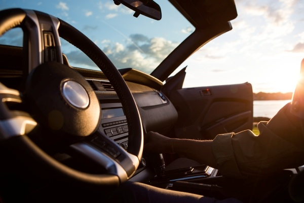 Close up of steering wheel and dashboard of a convertible while light shines in