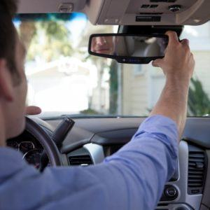 man checking rear view mirror