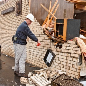 a man inspecting a wrecked building after a severe storm