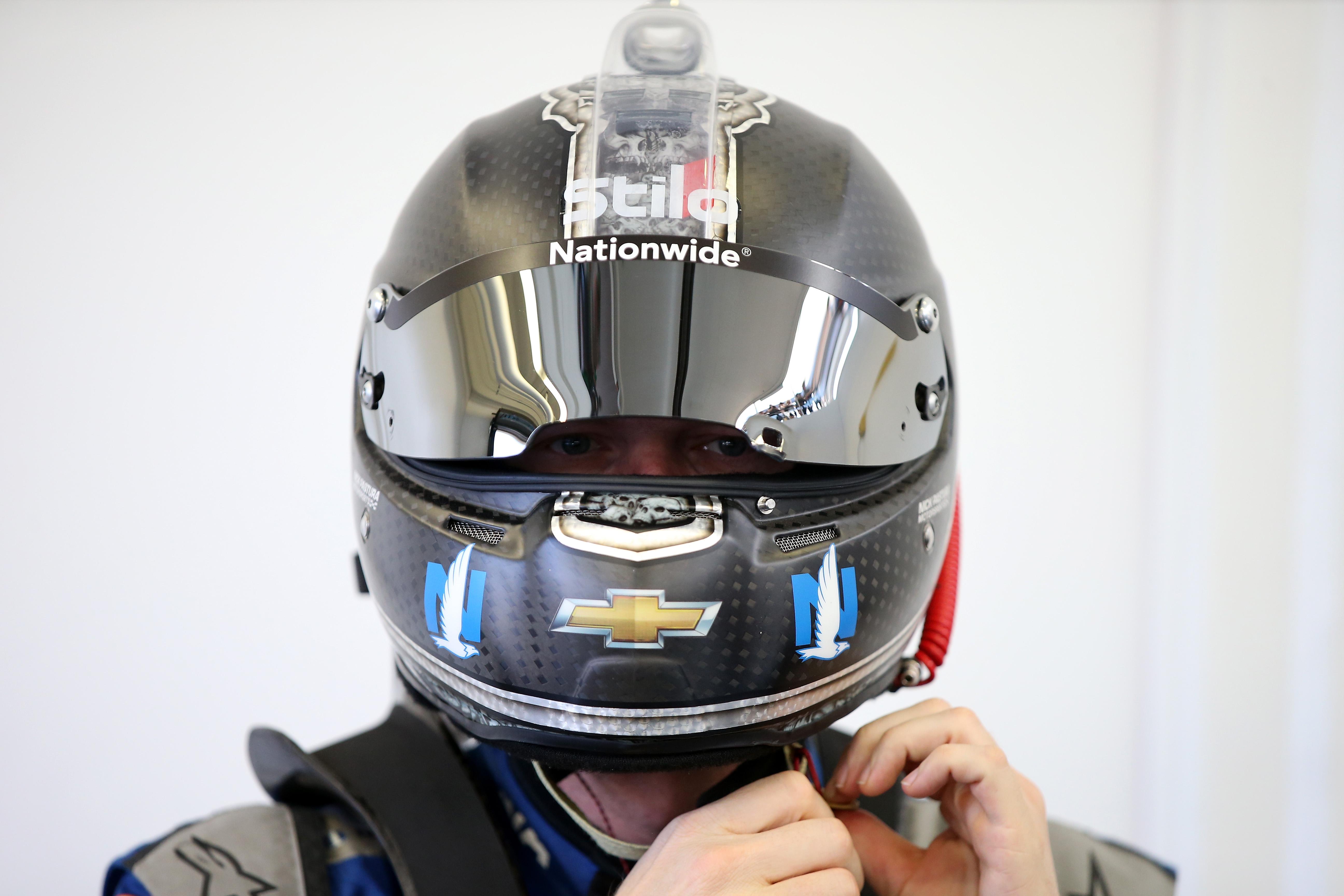 a NASCAR driver securing a helmet
