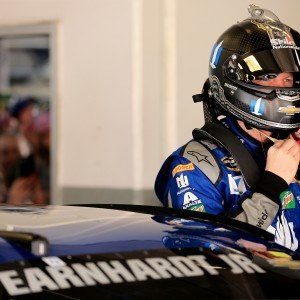 a NASCAR driver putting on a helmet