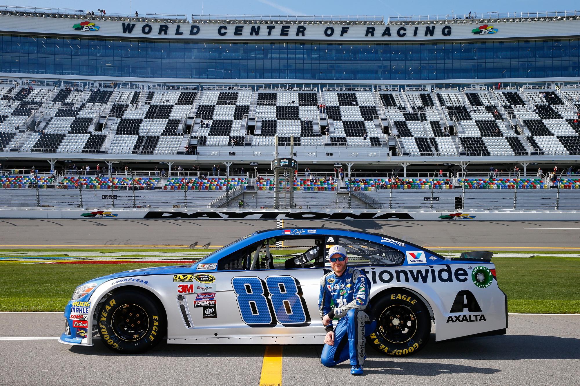 a NASCAR driver kneeling by a race car