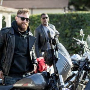 two men standing near motorcycles