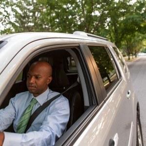 man wearing tie driving car