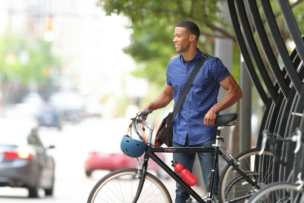 man in blue shirt standing next to bicycle