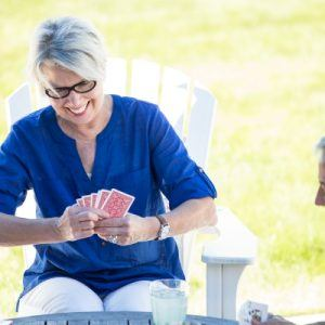 older woman playing cards outside