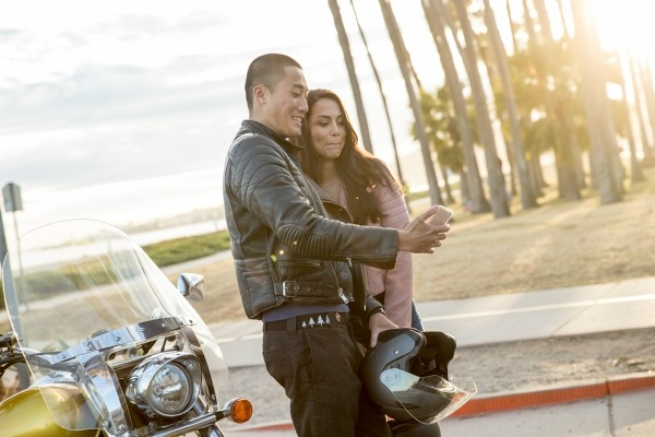 Couple standing next to motorcycle looking at cell phone and smiling