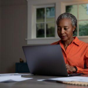 woman in orange shirt working on computer