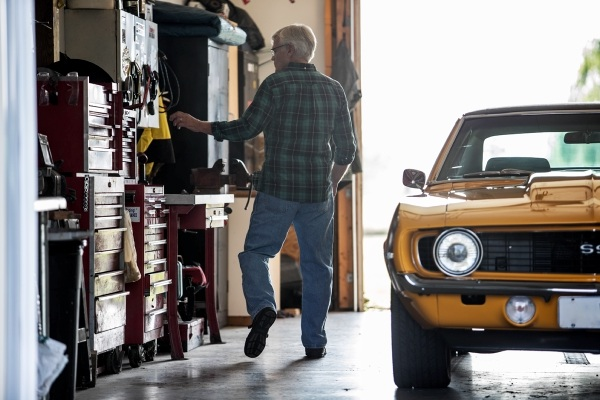 a man and a yellow car in a garage