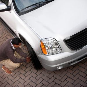 man fixing car tire