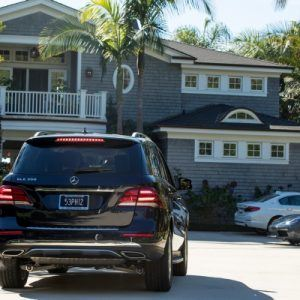 Black SUV parked in front of big house