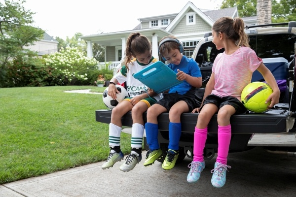 kids playing with tablet on tailgate of truck