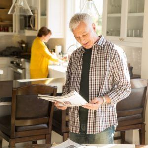 Woman in yellow shirt washing dishes in sink while man holds paper