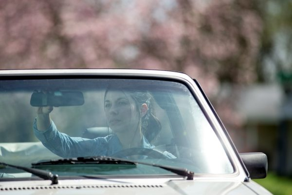 teenage girl adjusting the rear view mirror in a convertible