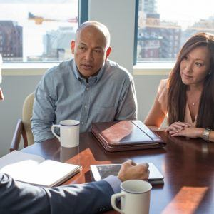 Couple discusses finances at a table with their advisor